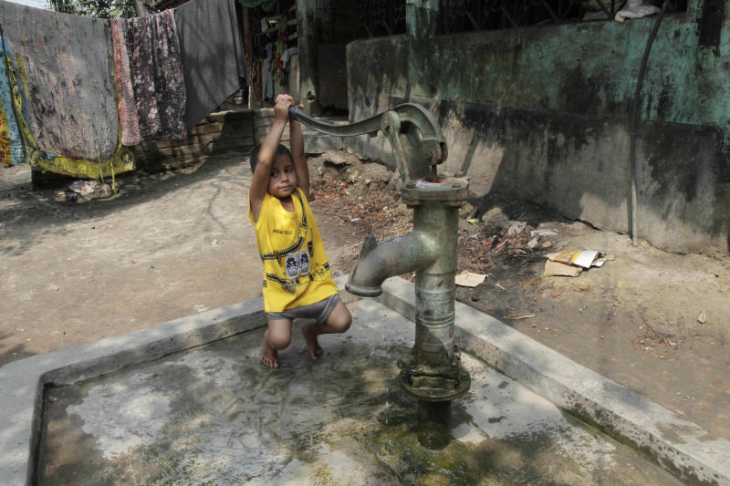 Rukhsar Khatoon, the last person in India to contract polio, hangs on the handle of a tube well in Shahpara Village, 60 kilometers (40 miles) west of Kolkata, India, Thursday, March 27, 2014. In India, the scourge of polio ends with Khatoon, a lively 4-year-old girl who contracted the disease when she was a baby after her parents forgot to get her vaccinated. On Thursday, after three years with no new cases, the World Health Organization formally declared India polio-free. (AP Photo/Bikas Das)