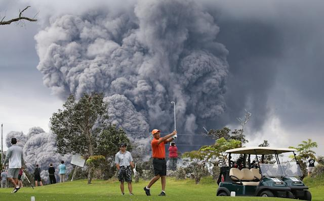 <p>People play golf as an ash plume rises in the distance from the Kilauea volcano on Hawaii's Big Island on May 15, 2018 in Hawaii Volcanoes National Park, Hawaii. (Photo: Mario Tama/Getty Images) </p>