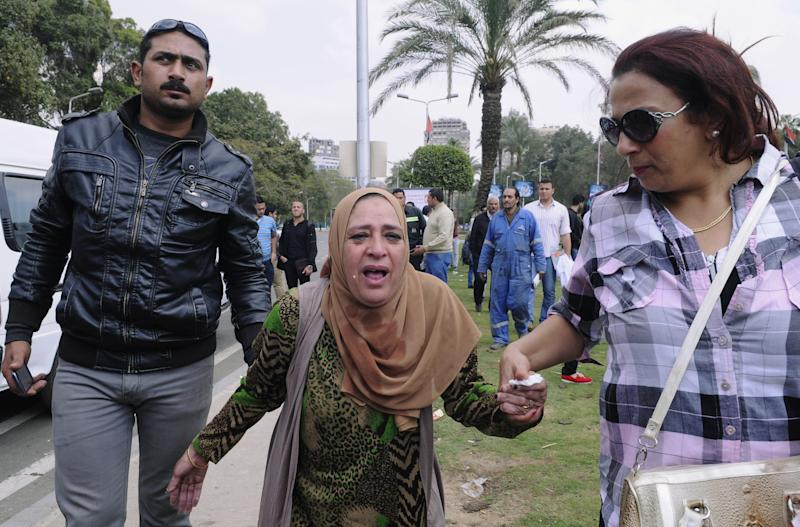 An Egyptian woman, center, is escorted out of the site of multiple bombings outside the main campus of Cairo University in Giza, near downtown Cairo, Egypt, Wednesday, April 2, 2014. The bombings targeted riot police routinely deployed at the location in anticipation of near-daily protests by students who support ousted Islamist President Mohammed Morsi and his Muslim Brotherhood group. (AP Photo/Mohammed Asad)