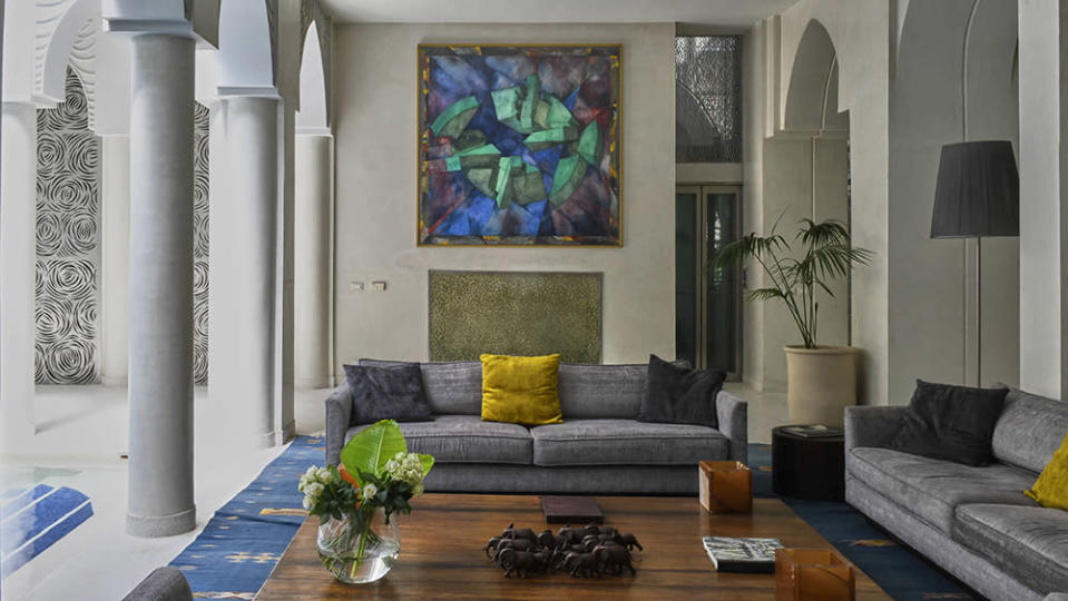 A sitting room that blends modern furniture and an abstract painting by Giò Pomodoro with traditional Moroccan architecture's arches and metalwork. - Credit: Jean Cazals