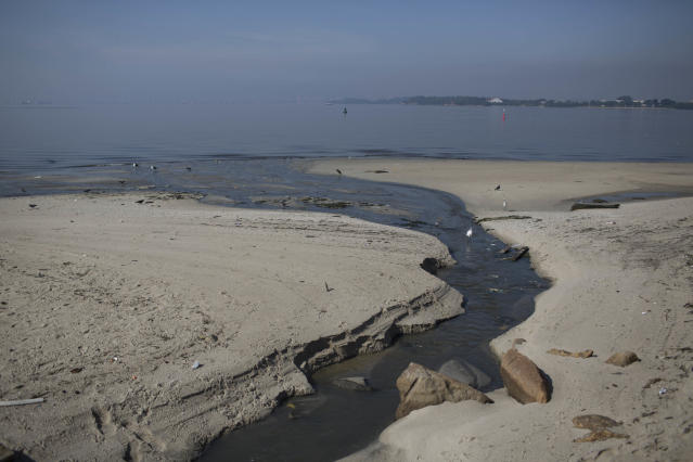 FILE - In this May 15, 2014 file photo, untreated sewage creates a dark streak on the sand as it flows into the water of Guanabara Bay in Rio de Janeiro, Brazil. Rio de Janeiro Mayor Eduardo Paes said Saturday, June 7, 2014 that the city will fail to keep the promise of cleaning polluted Guanabara Bay for the 2016 Olympics, which it made five years ago when it was awarded the games. (AP Photo/Felipe Dana, File)