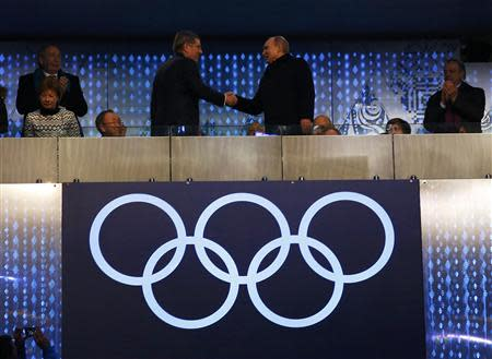 President of Russia, Vladimir Putin (R) shakes hands with International Olympic Committee President Thomas Bach, as Secretary-General of the United Nations Ban Ki-moon looks on during the opening ceremony of the 2014 Sochi Winter Olympics, February 7, 2014. REUTERS/Brian Snyder