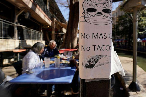 PHOTO: A sign requiring masks is seen near diners eating at a restaurant on the River Walk, March 3, 2021, in San Antonio. (Eric Gay/AP)