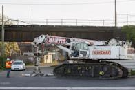 A worker gestures as a large crane arrives to help with the aftermath of a derailed Amtrak train in Philadelphia, Pennsylvania May 13, 2015. An Amtrak passenger train with more than 200 passengers on board derailed in north Philadelphia on Tuesday night, killing at least five people and injuring more than 50 others, several of them critically, authorities said. Authorities said they had no idea what caused the train wreck, which left some demolished rail cars strewn upside down and on their sides in the city's Port Richmond neighborhood along the Delaware River. REUTERS/Lucas Jackson