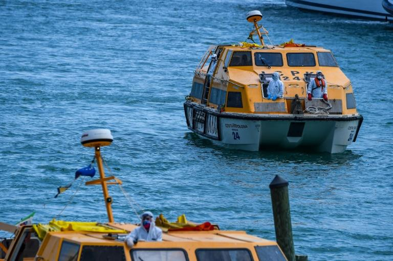 Sick crew members from two cruise ships are transported to shore in two smaller boats in Miami on March 26 (AFP Photo/CHANDAN KHANNA)