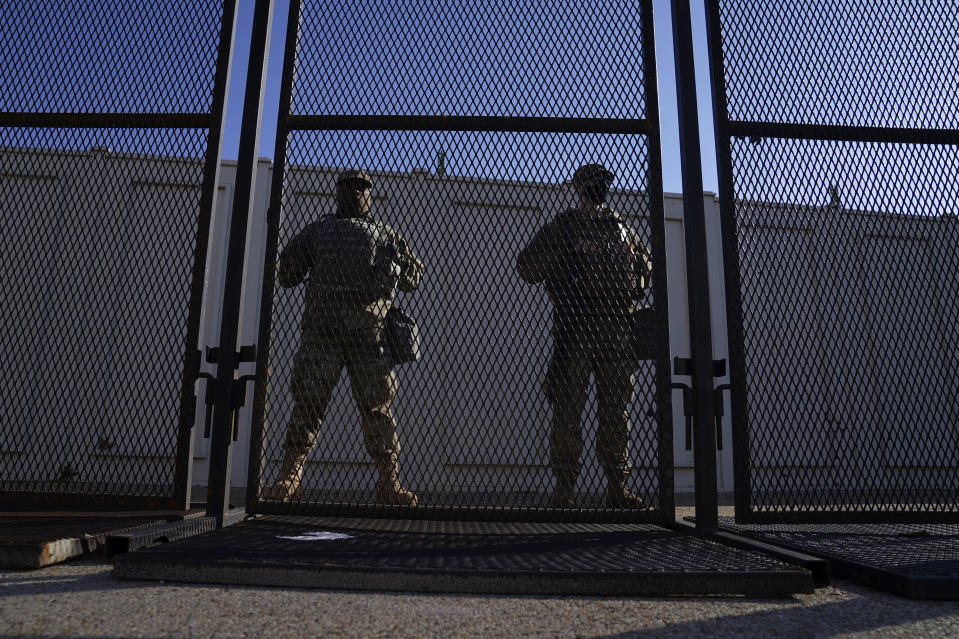 National Guard members stand behind a fence near the U.S. Capitol on Saturday, Jan. 16, 2021, in Washington as security is increased ahead of the inauguration of President-elect Joe Biden and Vice President-elect Kamala Harris. (AP Photo/John Minchillo)