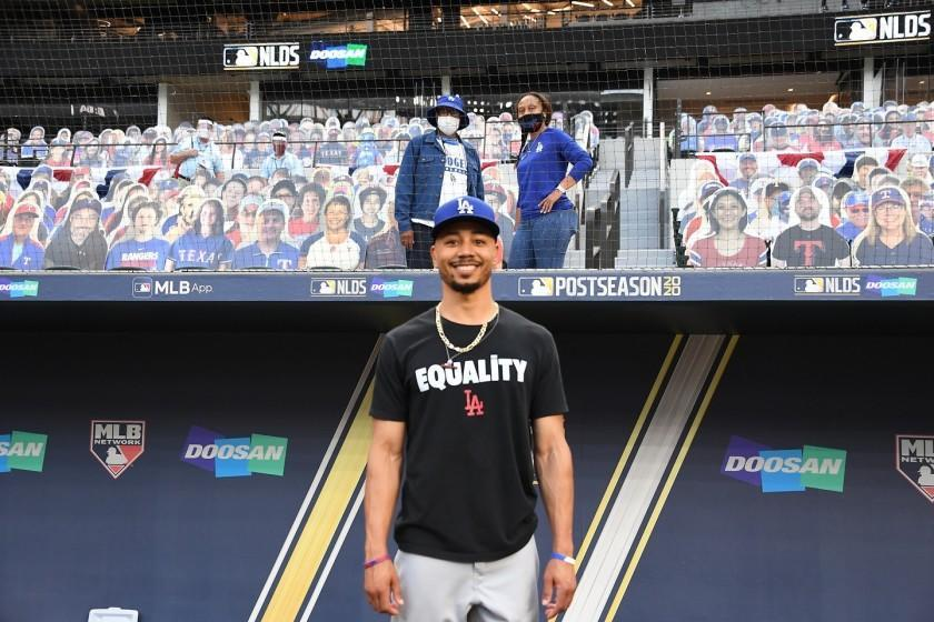 Dodgers outfielder Mookie Betts stands in front of family.