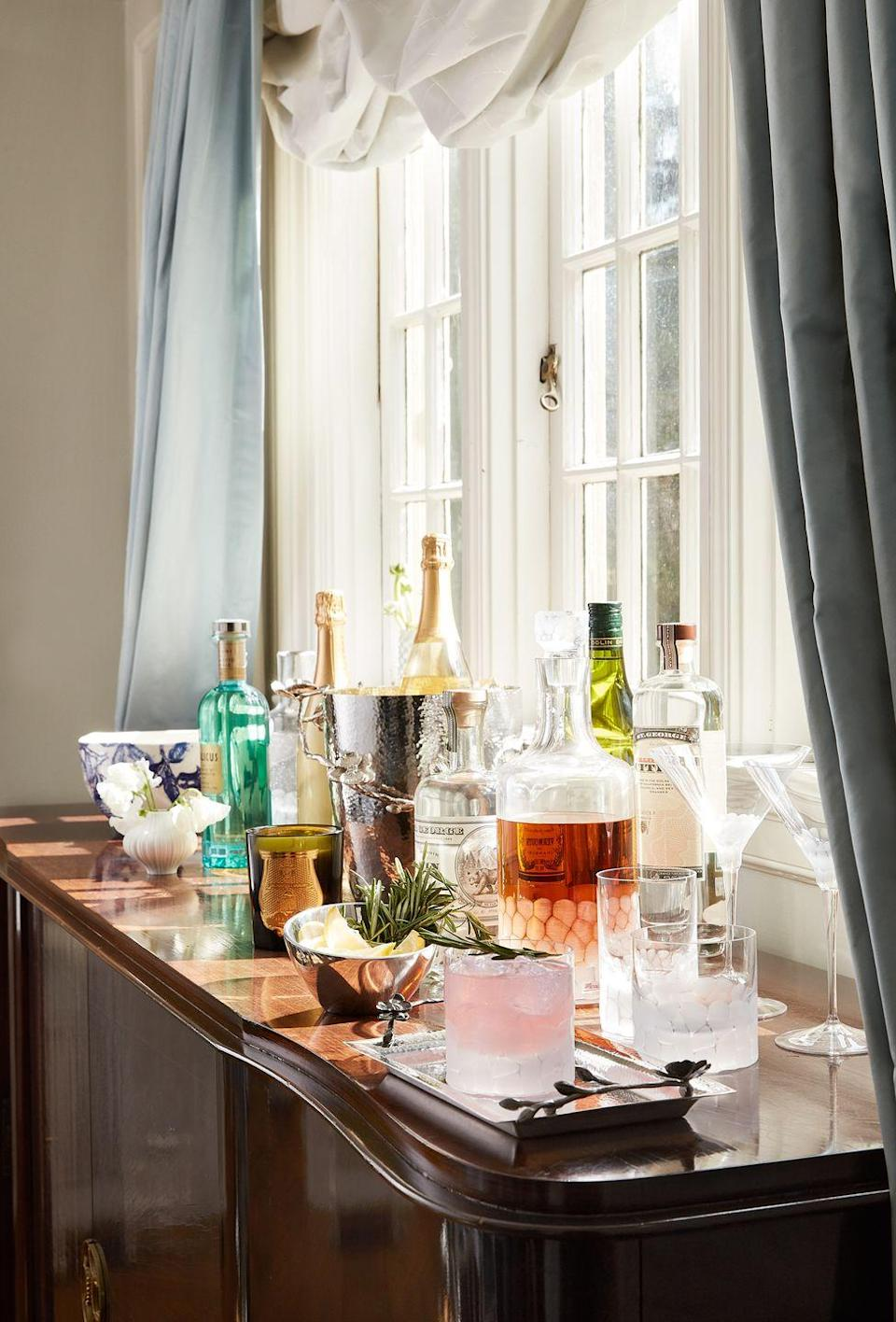 """<p>Even if your bar is not one that can easily move about, it's imperative to keep it styled in interesting ways to keep the space feeling novel, especially when entertaining. New York City interior designer <a href=""""http://www.younghuh.com"""" rel=""""nofollow noopener"""" target=""""_blank"""" data-ylk=""""slk:Young Huh"""" class=""""link rapid-noclick-resp"""">Young Huh</a> knows the power of this.</p><p>""""I say: Always style a bar with herbs. Some thyme or rosemary in a cocktail is a little surprising, smells so wonderful, and looks fantastic on a bar.""""</p><p> Dramatic drapery, fresh herbs from the garden, and a bud vase of blooms turn this bar a beautiful moment.</p>"""