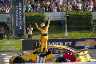 Fans cheer as Kyle Busch stands on the window opening of his race car and celebrates winning a NASCAR Cup Series auto race at Pocono Raceway, Sunday, June 27, 2021, in Long Pond, Pa. (AP Photo/Matt Slocum)