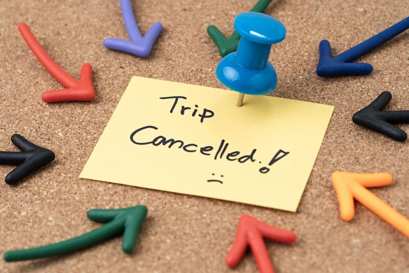 Flight cancelled due to COVID-19 virus spread outbreak, cancel plan to travel reminder concept, Thumbtack pushpin with multi arrows pointing to small paper note written the word Trip Cancelled.