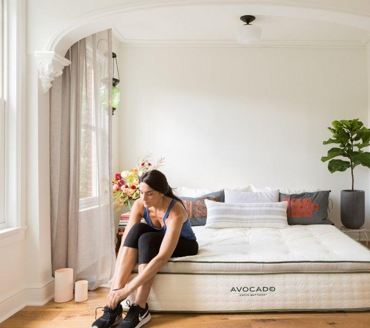 """<h3><a href=""""https://www.avocadogreenmattress.com/shop/avocado-mattress/"""" rel=""""nofollow noopener"""" target=""""_blank"""" data-ylk=""""slk:Avocado Green Mattress"""" class=""""link rapid-noclick-resp"""">Avocado Green Mattress</a></h3><br><strong>Mattress Type: </strong>Hybrid (Foam & Spring) <br><strong>Sleeper Style: </strong>Side & Stomach<br><strong>Pros: </strong>Eco-Friendly & Supportive<br><strong>Cons: </strong>Initial Firmness <br><br>""""My partner and I had been sleeping on an all-foam mattress but weren't totally satisfied due to our distinctly opposite sleep styles; while the softer memory foam worked well for me (a sound side sleeper), it wasn't supportive enough for him (a restless stomach sleeper). So, we went on the hunt for a hybrid compromise and settled on Avocado's Green Mattress (a combo of organic foam latex, wool, cotton, and pocketed support coils) — due in part to its eco-friendly ethos and for all the best mattress review buzz we'd been seeing.""""<br><br>""""We weren't sure what to expect but had been forewarned that the mattress is FIRM and does take some getting used to (many reviews highly recommended <a href=""""https://www.avocadogreenmattress.com/shop/mattress-topper/"""" rel=""""nofollow noopener"""" target=""""_blank"""" data-ylk=""""slk:the plush mattress topper"""" class=""""link rapid-noclick-resp"""">the plush mattress topper</a> for sleepers who preferred extra cushioning, aka me). The mattress arrived a few weeks before the topper came, completely compressed in a heavy but easy-enough-to-push-upstairs box. After snipping open the package and unfurling it from the box, we let it alone to decompress atop our bedframe before a first-night test run. At first glance, it looked and felt sturdy, soft, and well-made; all of the stitches, seams, and helpful side handles felt thoughtfully placed and sustainably crafted. We didn't notice any strange out-of-the-box smells, either!""""<br><br>""""The first night was, as is to be expected with any new mattress, restless. I spent half the night wrigglin"""