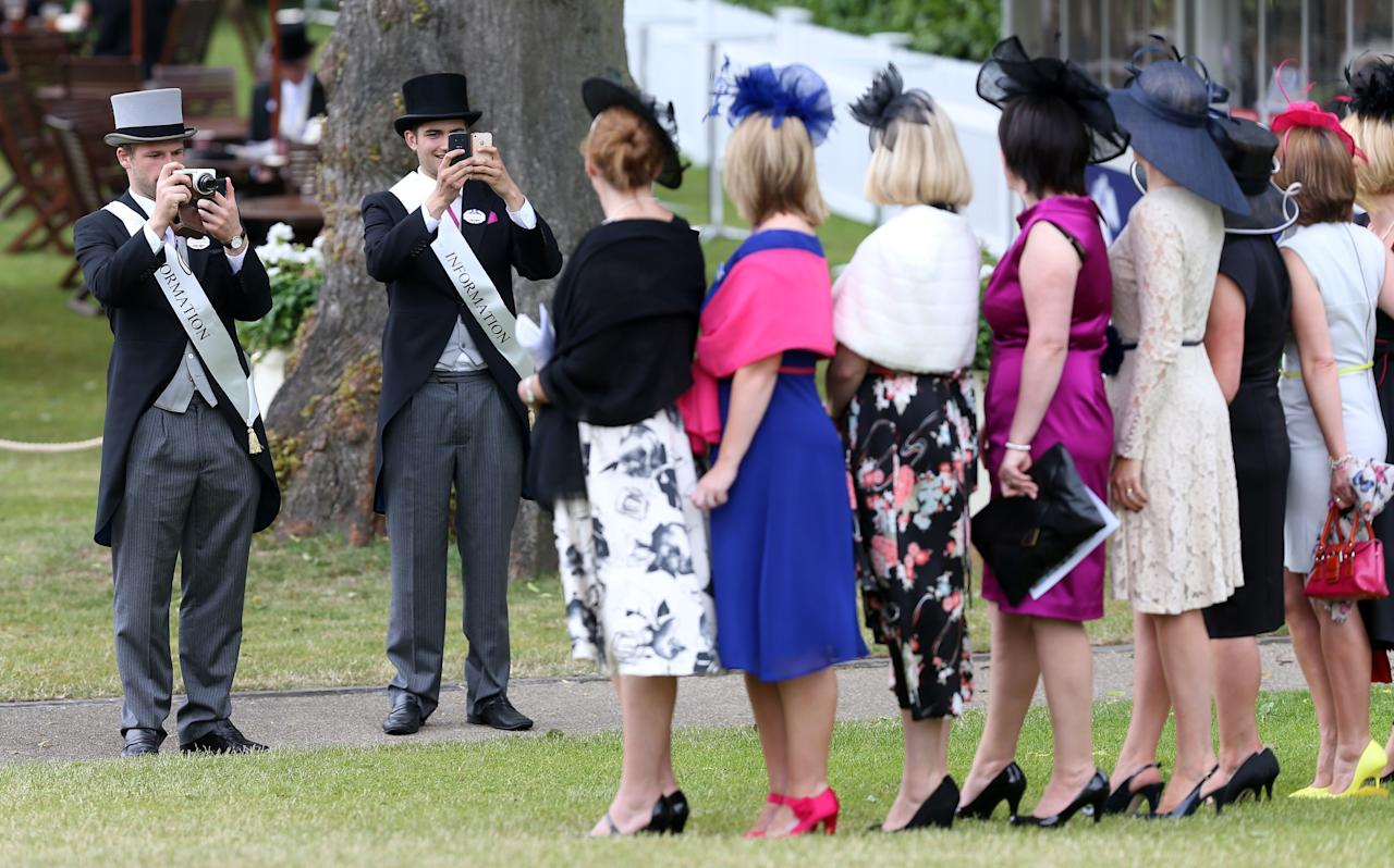 Ascot information helpers take photographers of female racegoers in the Royal enclosure using their camera's and phones during day four of the Royal Ascot meeting at Ascot Racecourse, Berkshire.