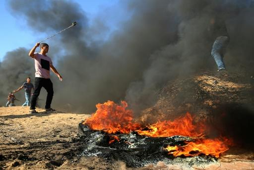 A Palestinian protester uses a slingshot next to burning tyres along the Israel-Gaza border on August 10, 2018