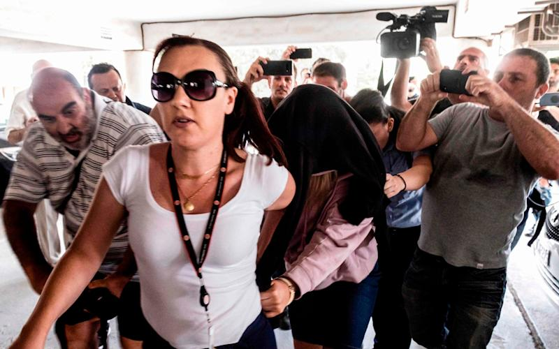 The British woman is led into a courthouse in Paralimni, Cyprus - AFP
