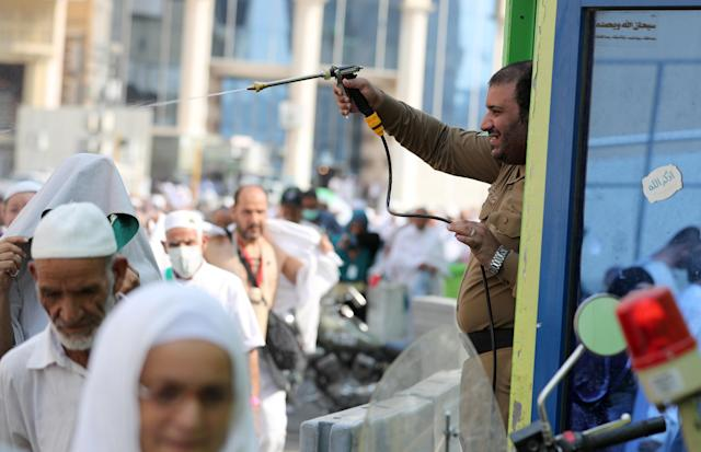<p>A Saudi policeman spays Muslim pilgrims with water to cool them off near the Grand Mosque in the holy Saudi city of Mecca, on Aug. 29, 2017, on the eve of the start of the annual hajj pilgrimage. (Photo: Karim Sahib/AFP/Getty Images) </p>