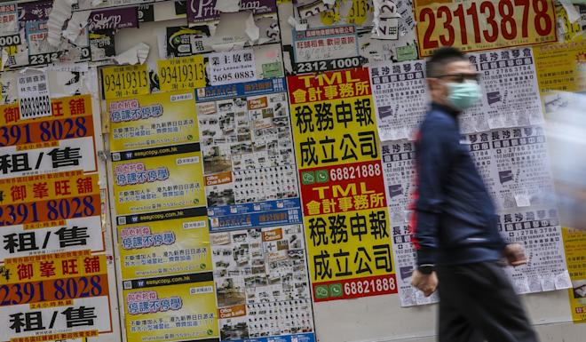 A pedestrian wearing a protective mask walks past a closed shop in the Mong Kok district of Hong Kong. Photo: K.Y. Cheng