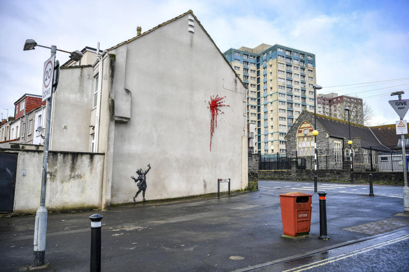 A new artwork on the side of a house in Bristol, England, Thursday Feb. 13, 2020, which has been confirmed as the work of street artist Banksy. (Ben Birchall/PA via AP)