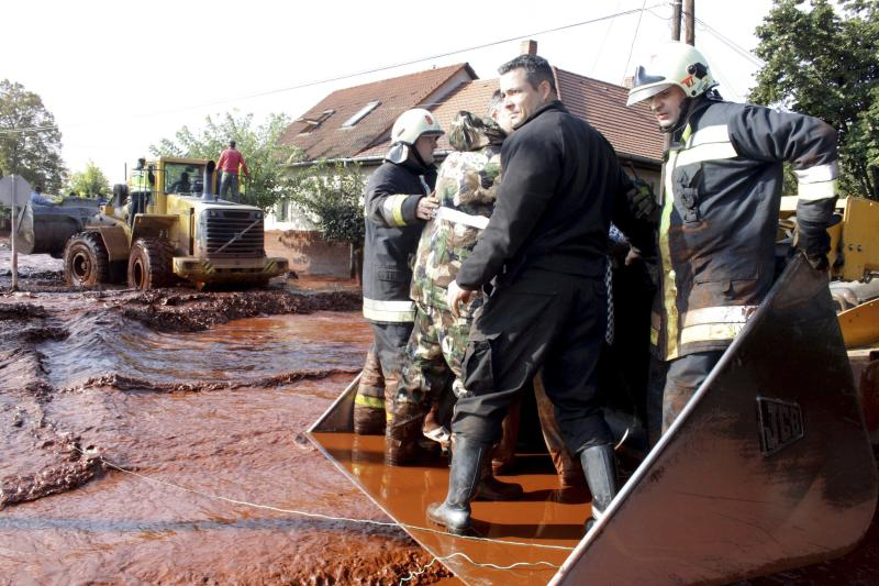 Local residents are rescued by excavators in Devecser, 164 kms southwest of Budapest, Hungary Monday Oct. 4, 2010.  Rescue services say the reservoir of an alumina plant in western Hungary has burst, flooding several towns including Devecser with red sludge. (AP Photo/MTI, Lajos Nagy)