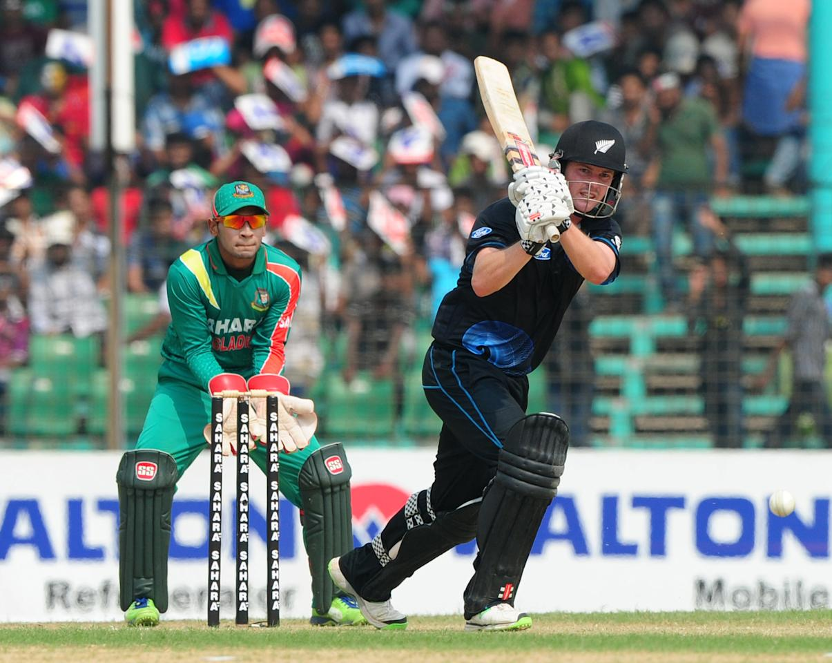 New Zealand batsman Colin Munro (R) plays a shot as Bangladesh captain Mushfiqur Rahim looks on during the third One-Day International (ODI) cricket match between Bangladesh and New Zealand at Khan Jahan Ali Stadium in Fatullah, on the outskirts of Dhaka on November 3, 2013.   AFP PHOTO/ Munir uz ZAMAN        (Photo credit should read MUNIR UZ ZAMAN/AFP/Getty Images)