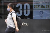 A man wearing a mask against the spread of the new coronavirus walks in front of a countdown calendar showing 30 days to start Tokyo 2020 Olympics Wednesday, June 23, 2021, in Tokyo. (AP Photo/Eugene Hoshiko)