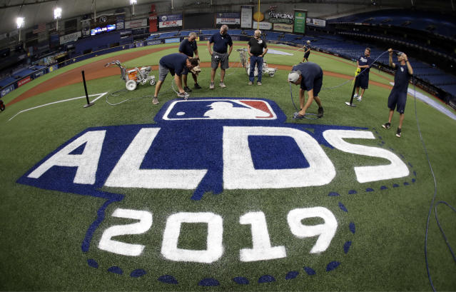 Members of the Tampa Bay Rays grounds crew spray-paint the ALDS logo on the field Sunday, Oct. 6, 2019, in St. Petersburg, Fla. The Rays take on the Houston Astros in Game 3 of a baseball American League Division Series on Monday. (AP Photo/Chris O'Meara)