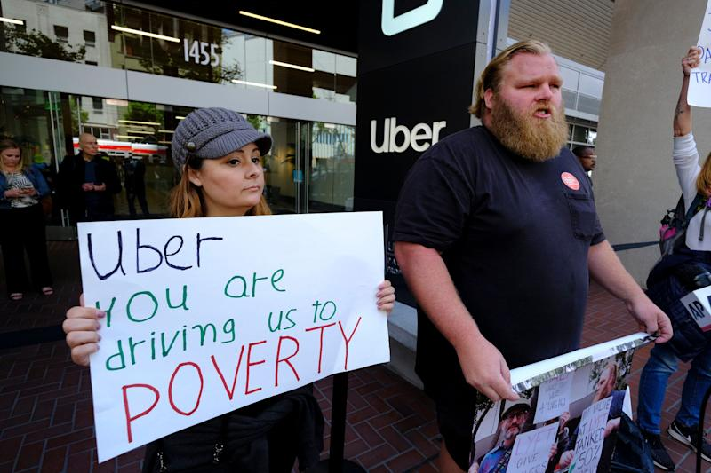 Annette Ribero, left, of San Jose, and Jeff Terry, of Sacramento, hold signs during a demonstration outside of Uber headquarters Wednesday, May 8, 2019, in San Francisco. Some drivers for ride-hailing giants Uber and Lyft turned off their apps to protest what they say are declining wages as both companies rake in billions of dollars from investors. Demonstrations in 10 U.S. cities took place Wednesday, including New York, Chicago, Los Angeles, San Francisco and Washington, D.C. The protests take place just before Uber becomes a publicly traded company Friday. (AP Photo/Eric Risberg)