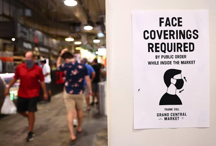 """<span class=""""caption"""">Signs like this may become more common as localities consider CDC guidelines.</span> <span class=""""attribution""""><a class=""""link rapid-noclick-resp"""" href=""""https://www.gettyimages.com/detail/news-photo/sign-is-posted-about-required-face-coverings-in-grand-news-photo/1329567933"""" rel=""""nofollow noopener"""" target=""""_blank"""" data-ylk=""""slk:Mario Tama/Getty Images"""">Mario Tama/Getty Images</a></span>"""