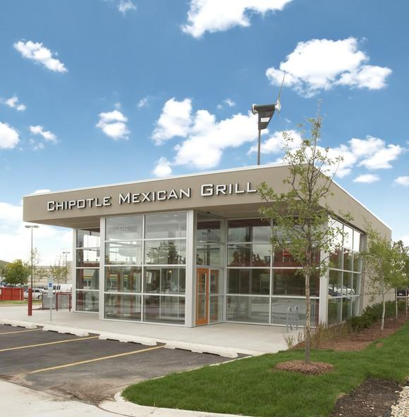An all-glass Chipotle restaurant on a sunny day with blue skies and puffy white clouds.