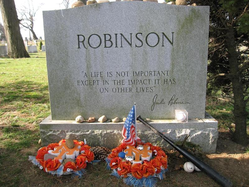 "This April 9, 2013 photo shows Jackie Robinson's gravesite, where fans still leave tributes to the man who integrated Major League Baseball when he joined the Brooklyn Dodgers in 1947. A new movie, ""42,"" about Robinson's life is bringing his inspiring story to a new generation. Fans young and old can find a number of places in Brooklyn connected to Robinson, including his burial site in Cypress Hills Cemetery, which straddles the border of Brooklyn and Queens and is reachable via the Jackie Robinson Parkway. (AP Photo/Beth J. Harpaz)"