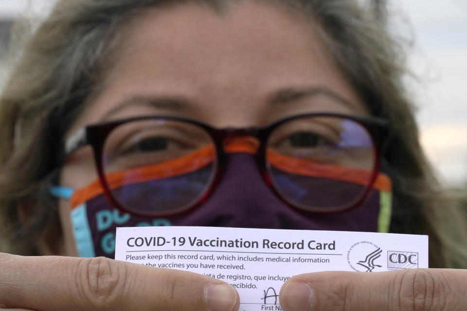 Alejandra poses with her vaccination card after getting her second Moderna COVID-19 shot Monday April 19, 2021, in Pasadena, Texas. Alejandra, a dentist who also lives in Monterrey, Mexico, said she decided to seek a vaccine in the U.S. shortly after losing her mother to COVID-19 in February. Many people with the means from Latin America are traveling thousands of miles to get the COVID-19 vaccine in the United States because supplies are limited in their own countries. (AP Photo/David J. Phillip)