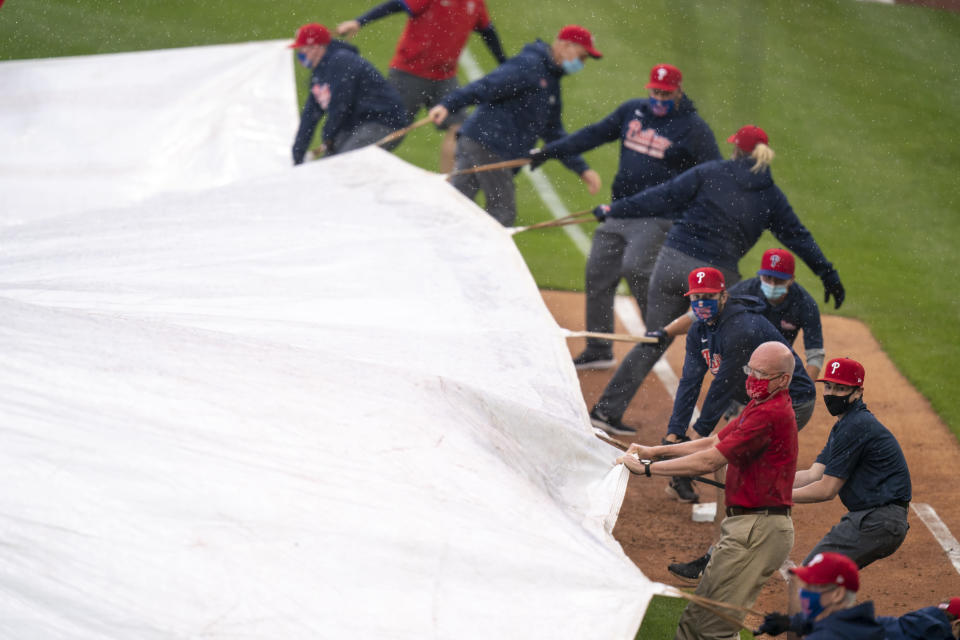 Philadelphia Phillies ground crew covers the field as a rain delay is called during the third inning of a baseball game against the San Francisco Giants, Wednesday, April 21, 2021, in Philadelphia. (AP Photo/Chris Szagola)