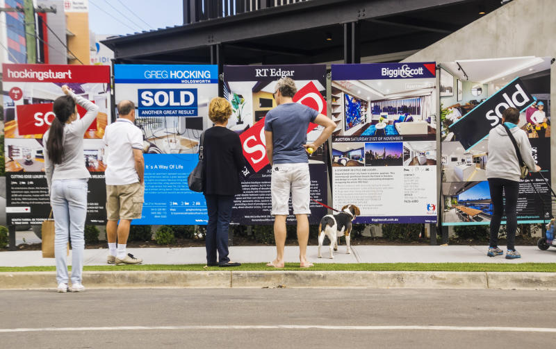 Melbourne, Australia - November 28, 2015: Visitors reading a row of estate agent signs outside a newly-renovated apartment building at 5 Commercial Rd, South Yarra. Formerly a derelict hotel, the site was the focus of Series 11 of popular Channel Nine TV series The Block. a reality renovation contest.