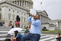 Abbas Alawieh, chief of staff for Rep. Cori Bush, D-Mo., takes a drink of water after sitting on the steps of Capitol Hill in Washington on Tuesday, Aug. 3, 2021. Bush has been camped outside the U.S. Capitol in protest of the eviction moratorium lapse, since the weekend.(AP Photo/Amanda Andrade-Rhoades)