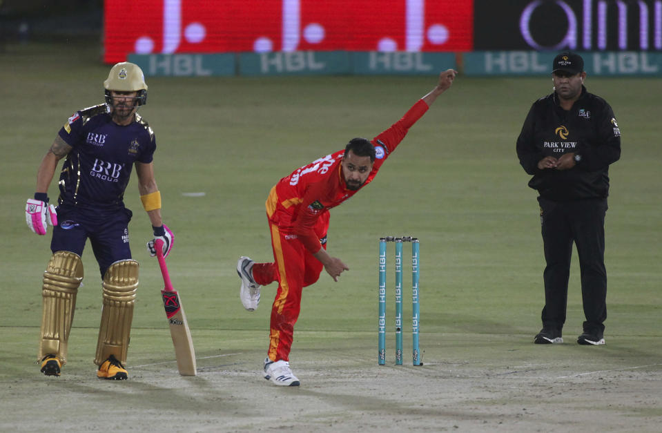 Islamabad United's Faheem Ashraf, center, delivers a ball while Quetta Gladiators' Faf du Plessis watches, during a Pakistan Super League T20 cricket match between Islamabad United and Quetta Gladiators at the National Stadium, in Karachi, Pakistan, Tuesday, March 2, 2021. (AP Photo/Fareed Khan)