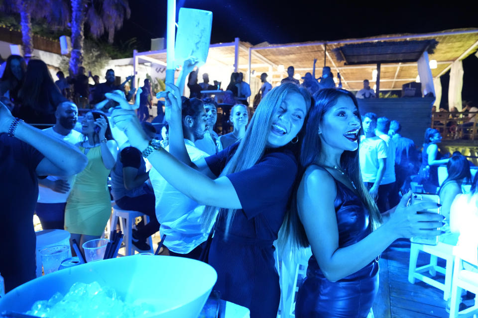 Women dance at the Taiga nightclub in Batroun village, north of Beirut, Lebanon, Friday, July 2, 2021. With their dollars trapped in the bank, a lack of functioning credit cards and travel restrictions imposed because of the pandemic, many Lebanese who traditionally vacationed over the summer at regional hotspots are also now turning toward domestic tourism. (AP Photo/Hassan Ammar)