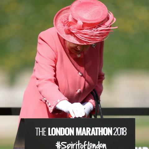 The Queen has pressed the start button and is wearing a bright coral outfit - Credit: WPA Pool/Getty Images