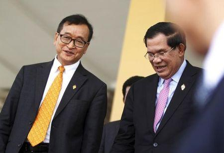 Cambodia's Prime Minister Hun Sen (R) and Sam Rainsy, president of the Cambodia National Rescue Party (CNRP), smile after a plenary session at the National Assembly in Phnom Penh