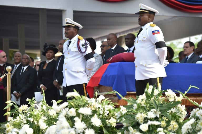 Police officers from the National Palace stand next to the casket of former Haitian president Rene Preval during the State Funeral at the kioske Occide Jeanty, in Port-au-Prince, on March 11, 2017