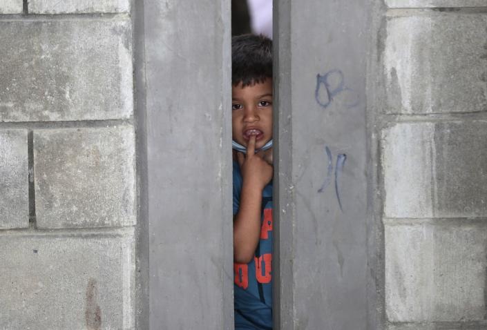 A boy peers from a migrant shelter in Arauquita, Colombia, Thursday, March 25, 2021, on the border with Venezuela. Thousands of Venezuelans are seeking shelter in Colombia this week following clashes between Venezuela's military and a Colombian armed group in a community along the nations' shared border. (AP Photo/Fernando Vergara)