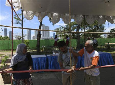 Volunteers make preparations at a polling station for the upcoming parliamentary election in Jakarta