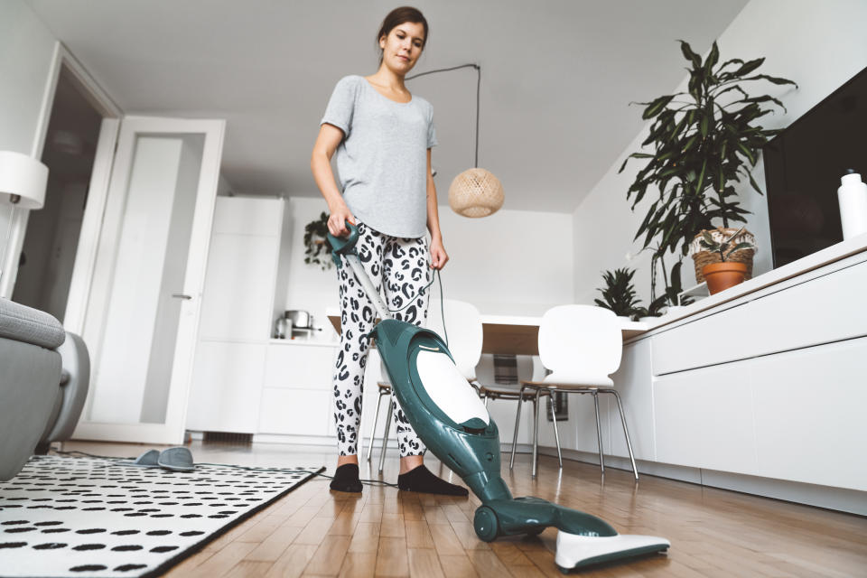 Young caucasian woman vacuuming wooden floors and carpet in the living room. Woman doing house chores, cleaning the floors.