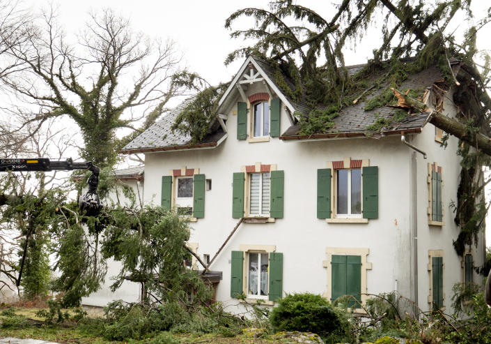 Trees have fallen on a house in Montmollin, Switzerland, Monday, Feb. 10, 2020. A storm battered the U.K. and northern Europe with hurricane-force winds and heavy rains Sunday, halting flights and trains and producing heaving seas that closed down ports. Soccer games, farmers' markets and cultural events were canceled as authorities urged millions of people to stay indoors, away from falling tree branches. (Laurent Darbellay/Keystone via AP)
