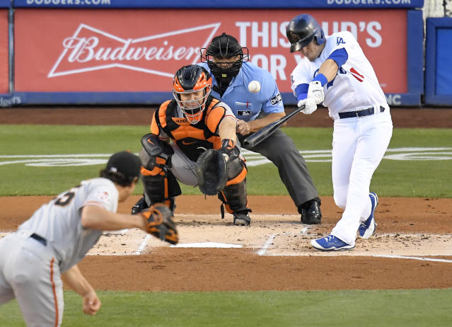 Los Angeles Dodgers' Enrique Hernandez, right, hits a solo home run as San Francisco Giants starting pitcher Derek Holland, left, and catcher Nick Hundley, second from left, watch along with home plate umpire Phil Cuzzi during the first inning of a baseball game Friday, June 15, 2018, in Los Angeles. (AP Photo/Mark J. Terrill)