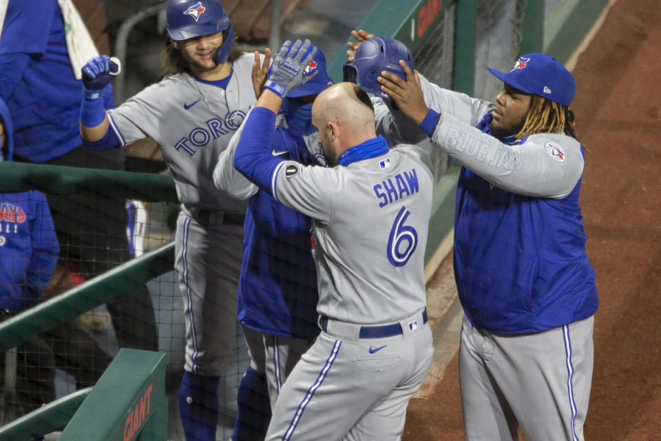 Toronto Blue Jays Travis Shaw is congratulated at the dugout after hitting a home run during the fifth inning of a baseball game against the Philadelphia Phillies, Saturday, Sept. 19, 2020, in Philadelphia. (AP Photo/Laurence Kesterson)