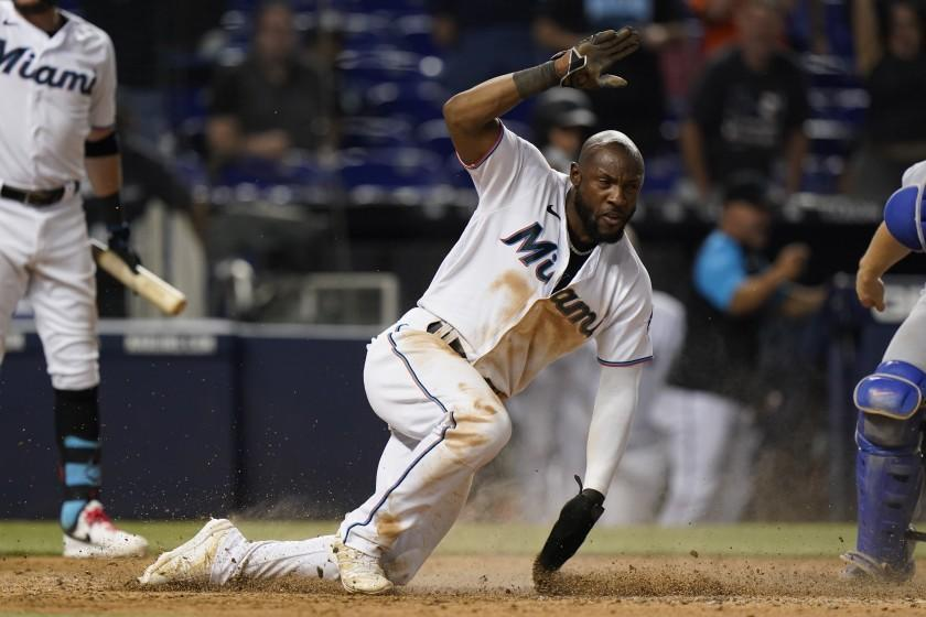Miami Marlins' Starling Marte slides into home to score on a throwing error by Los Angeles Dodgers catcher Will Smith after a wild pitch during the 10th inning of a baseball game Tuesday, July 6, 2021, in Miami. The Marlins won 2-1 in 10 innings. (AP Photo/Wilfredo Lee)