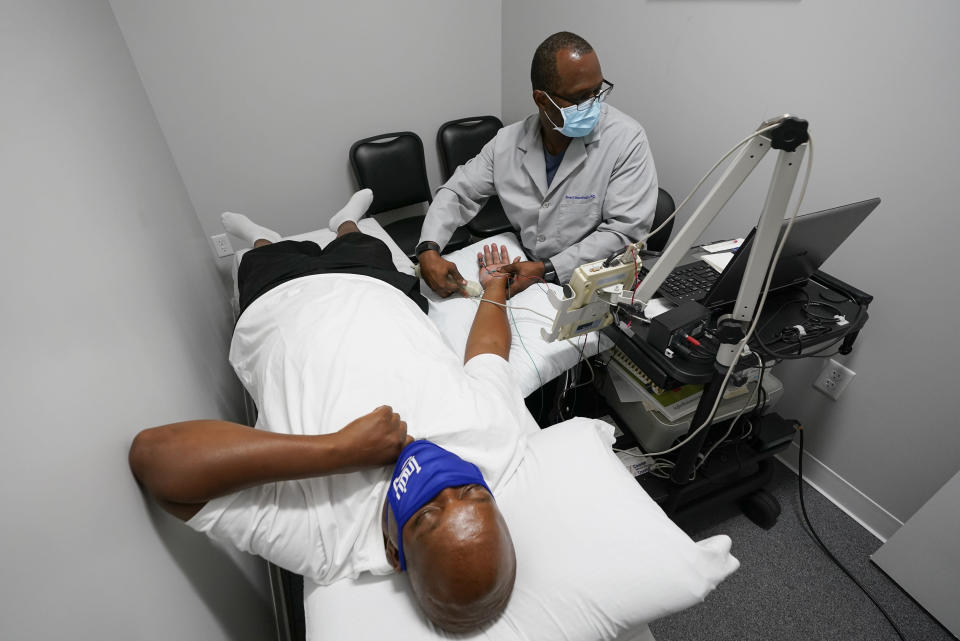 Larry Brown is tested by Dr. Jerry Smartt, Monday, Aug. 17, 2020, in Carmel, Ind. While hospitalized because of COVID-19 starting in March, doctors moved Brown to the ICU and started him on the ventilator while grappling with how to treat him. They tried the common antibiotic azithromycin, but his pneumonia grew worse. They administered the malaria treatment touted by President Donald Trump, hydroxychloroquine, but saw no progress. They put him in a medically induced coma, and attached him to an ECMO machine, which essentially did the job of his lungs by transferring oxygen into his blood. (AP Photo/Darron Cummings)