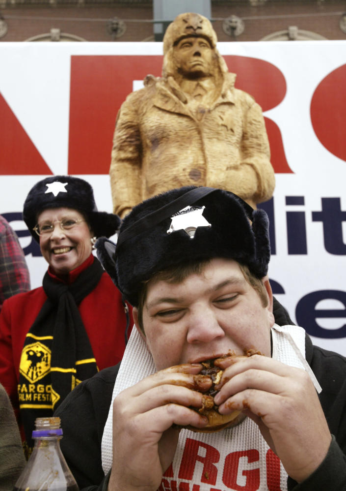 In this photo taken Sept. 25, 2003, Fargo Theatre executive director Margie Bailly looks on while Logan Kling of Fargo does his best to consume a roast beef sandwich during an eating contest held outside the theater in Fargo, N.D. When the movie Fargo debuted in 1996, many residents in the North Dakota city were not fans of the film's dark humor, not to mention the heavy accents. But the fame and cash from the movie eventually brought many Fargo residents around. Now, 16 years later, Fargo awaits the debut of a new cable television show by the same name. And many residents are less apprehensive about how their hometown will be portrayed this time around. (AP Photo/The Forum, Darren Gibbins)