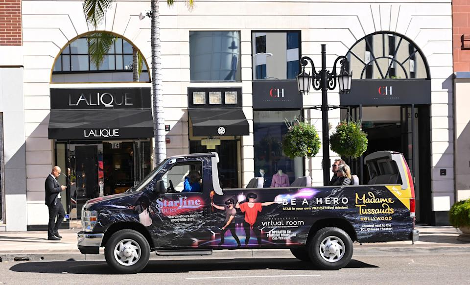 A sightseeing tour cruises past shops on Rodeo Drive in Beverly Hills in 2019.