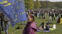 "A woman stands next to a flag as people gather at the Bois de la Cambre park for a party called ""La Boum 2"" in Brussels, Saturday, May 1, 2021. Police put on extra patrols Saturday to monitor the gathering which is being held in defiance of Belgium's current COVID-19 regulations. (AP Photo/Olivier Matthys)"