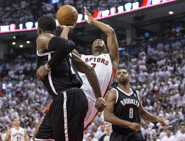 Toronto Raptors' Kyle Lowry is fouled as he drives between Brooklyn Nets' Joe Johnson, left, and Alan Anderson during the first half of Game 1 of an opening-round NBA basketball playoff series, in Toronto on Saturday, April 19, 2014. (AP Photo/The Canadian Press, Chris Young)